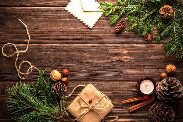 Flat lay photo of christmas presents, pine cones, cinnamon sticks and christmas tree branches.