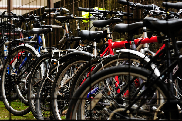 Image of various coloured bicycles locked on cycle stands