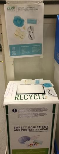 Photo of a recycling box with posters indicating that it is suitable for safety equipment and protective gear such as gloves, goggles and face masks.